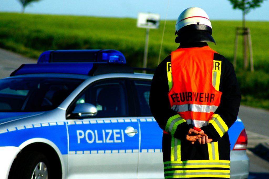 Feuerwehrmann vor Polizeiwagen