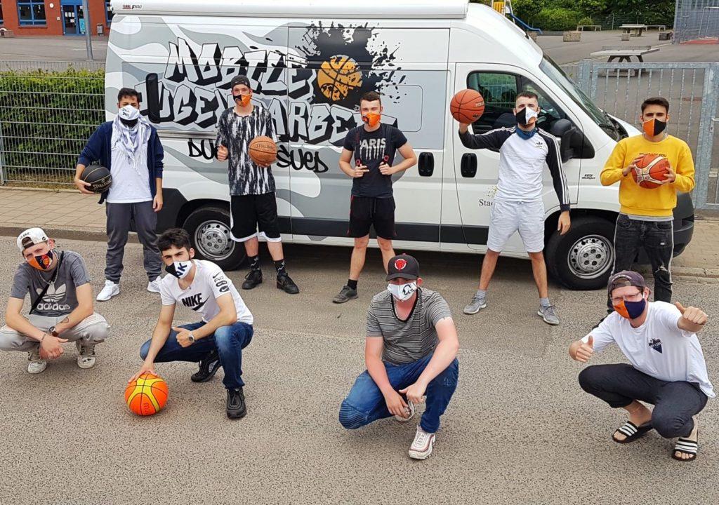 Jugendliche Basketballer mit bunten Masken