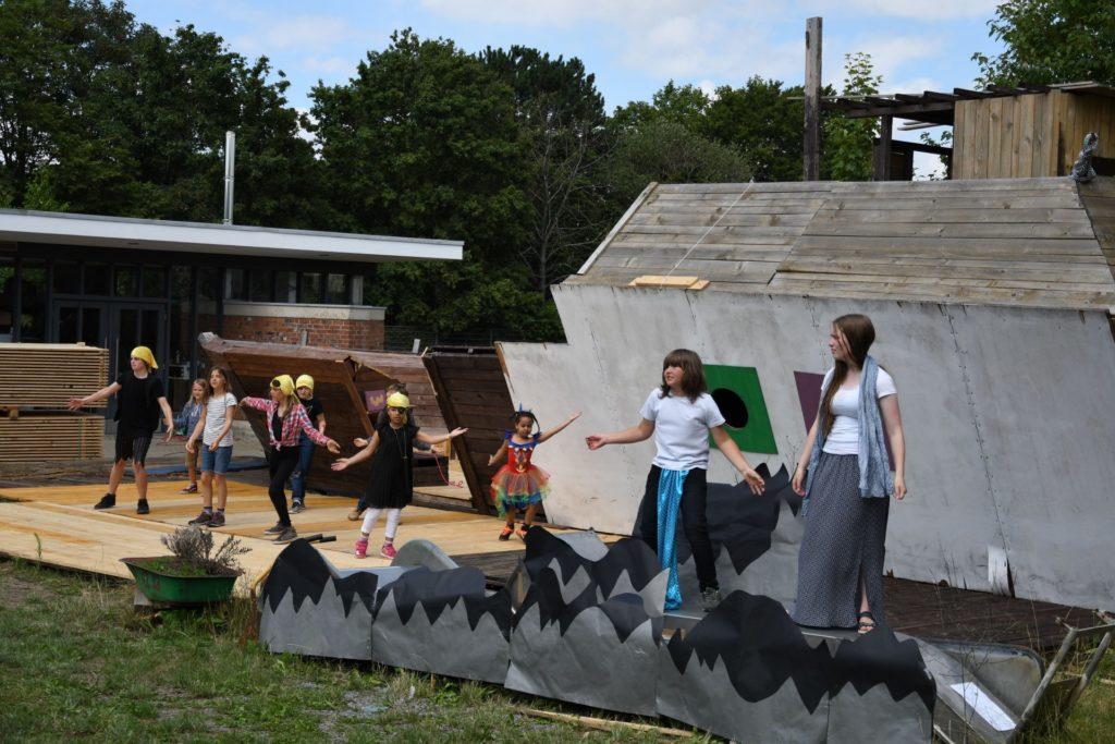 Eine Tanzszene aus dem Theaterstück vor dem großen Holzschff als Kulisse