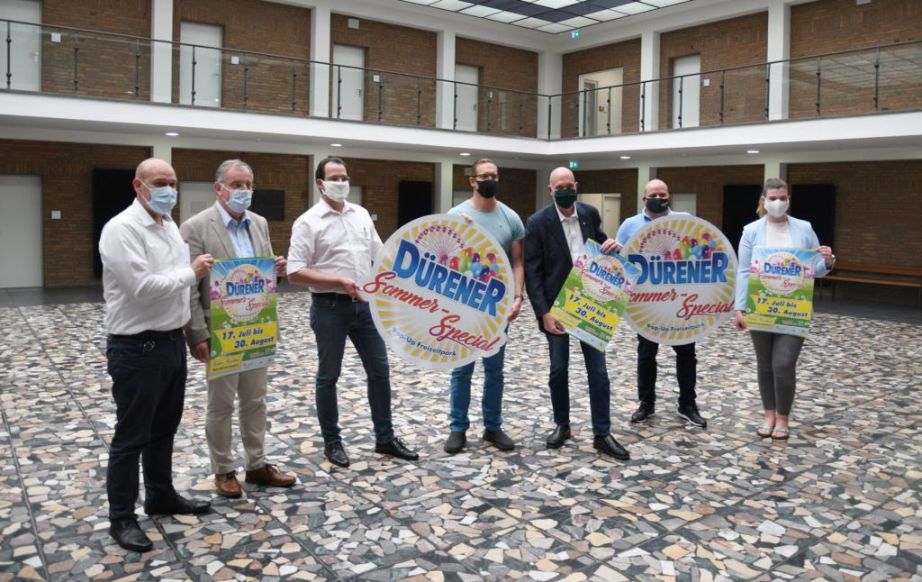 Vertreter der Stadt Düren und des VRS zeigen Logo und Plakat zum Sommer Special