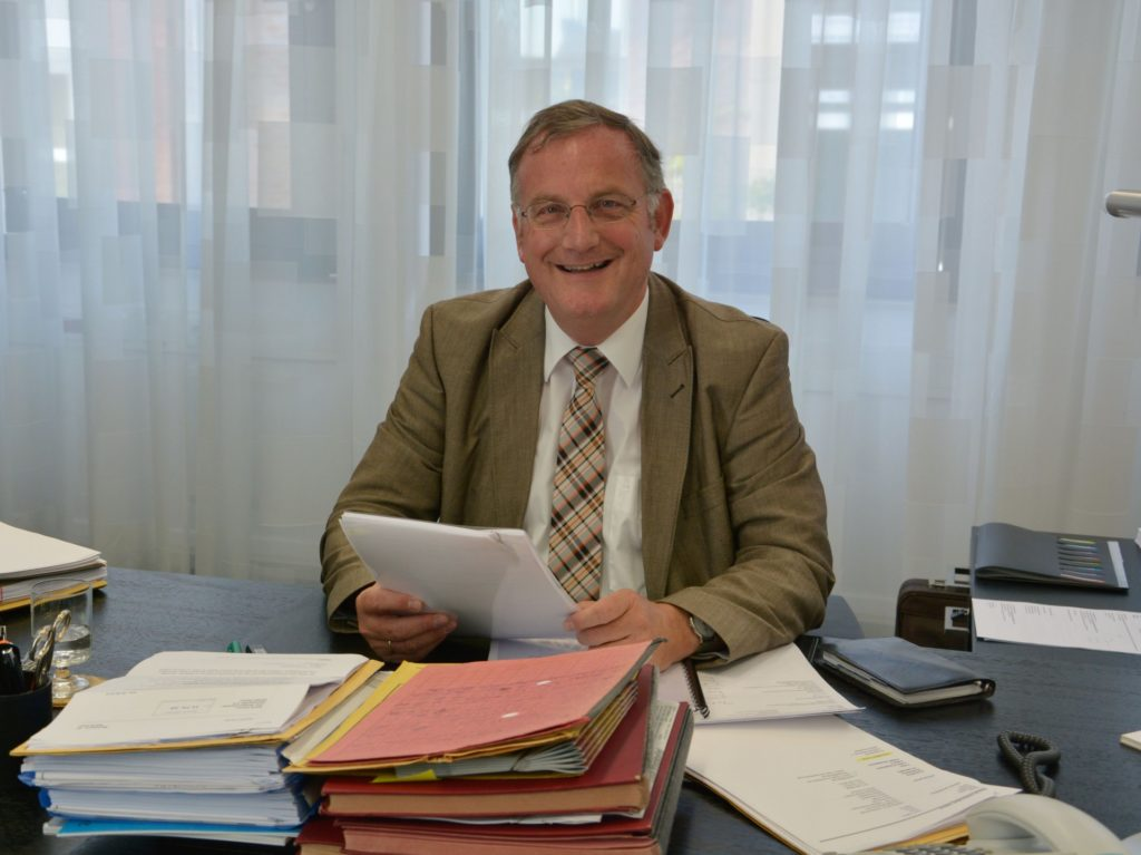 Bürgermeister Paul Larue am Schreibtisch sitzend.