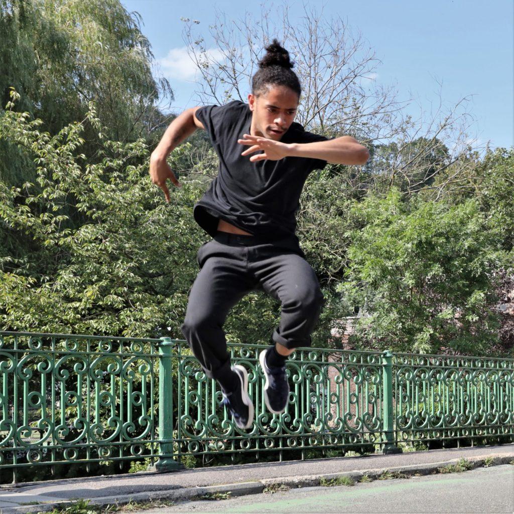 Ein Tänzer springt inmitten einer Stadtlandschaft