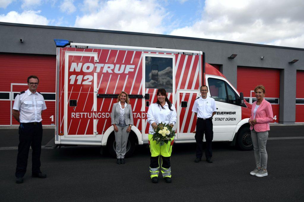 Sonja Skorupa mit zwei Feuerwehrkollegen, der Gleichstellungsbeauftragten und der Beigeordneten vor einem Feuerwehrwagen