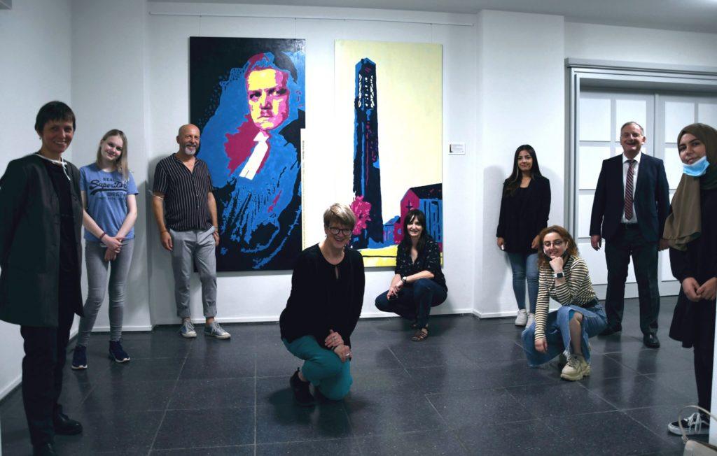 Bürgermeister, Schülerinnen und Lehrer vor dem Bilderpaar Wilhelm Wester im Rathausfoyer