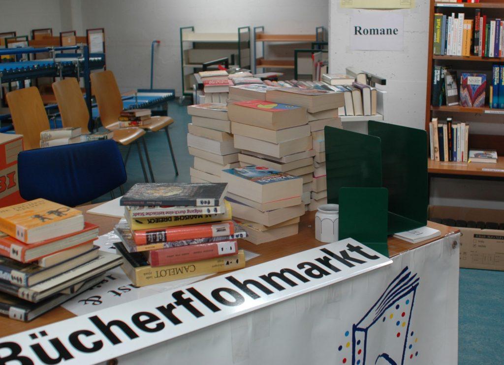 Bücherberge und ein Schild Bücherflohmarkt