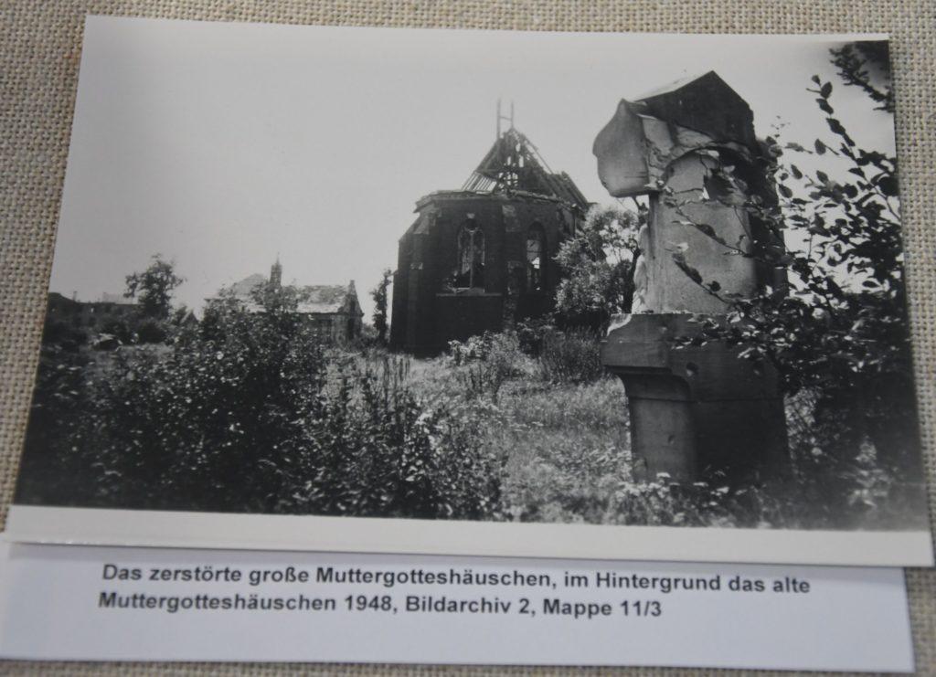Das im Krieg zerstörte große Muttergotteshäuschen, dahinter das beschädigte alte