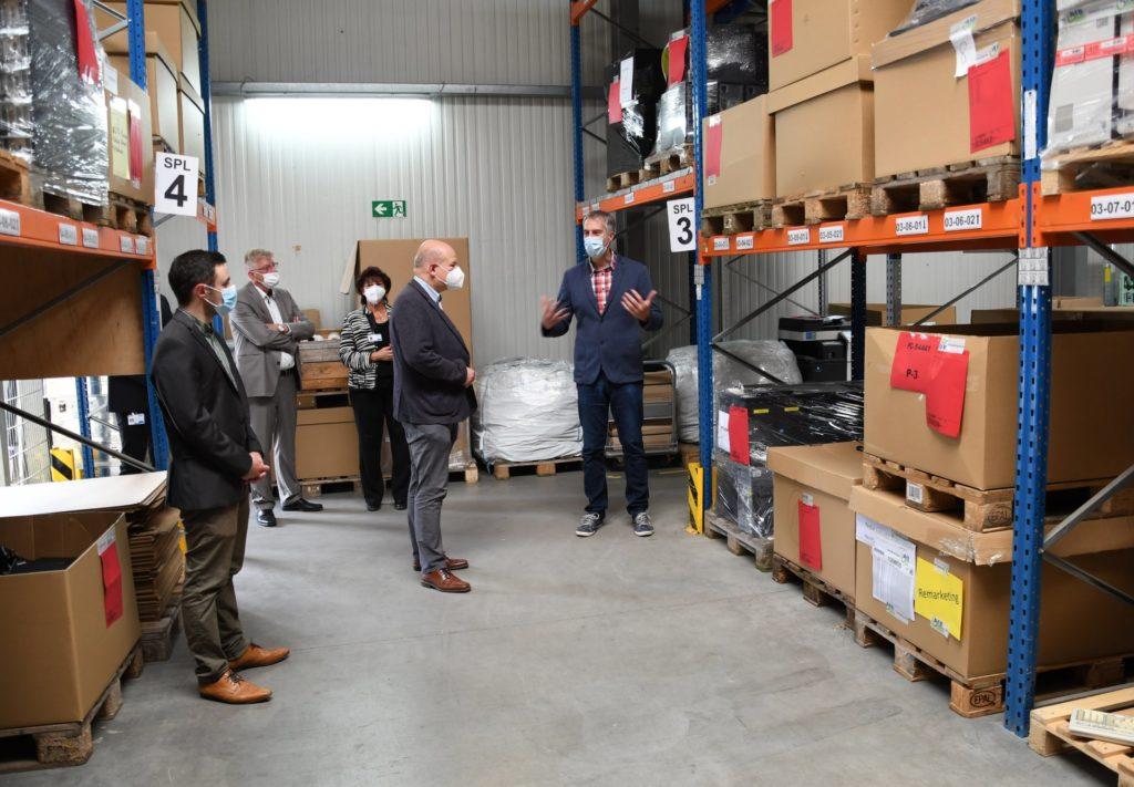 AfB-Niederlassungsleiter Dominik Lenke erklärt Bürgermeister Ullrich den Prozess des IT-Refurbishments. Hier sind generalüberholte PCs zu sehen.
